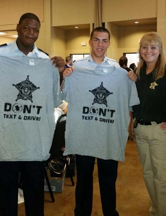 "Officers holding ""Don't text and drive"" t-shirts"