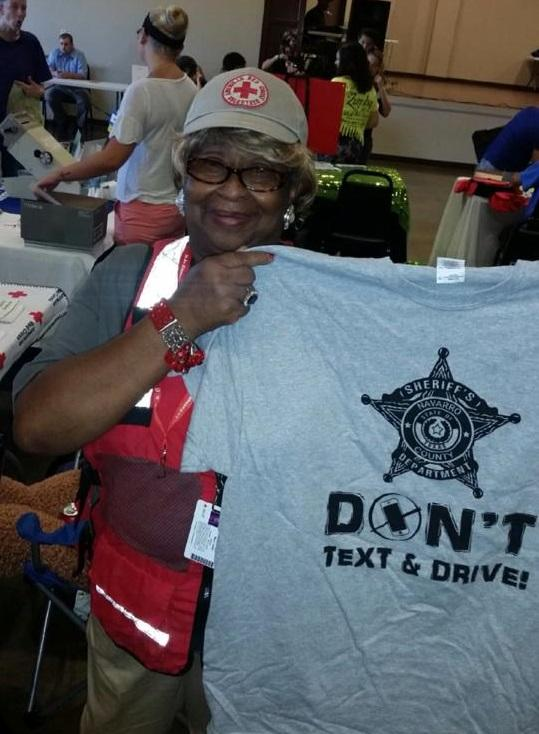 "Woman holding a ""Don't text and drive"" t-shirt"
