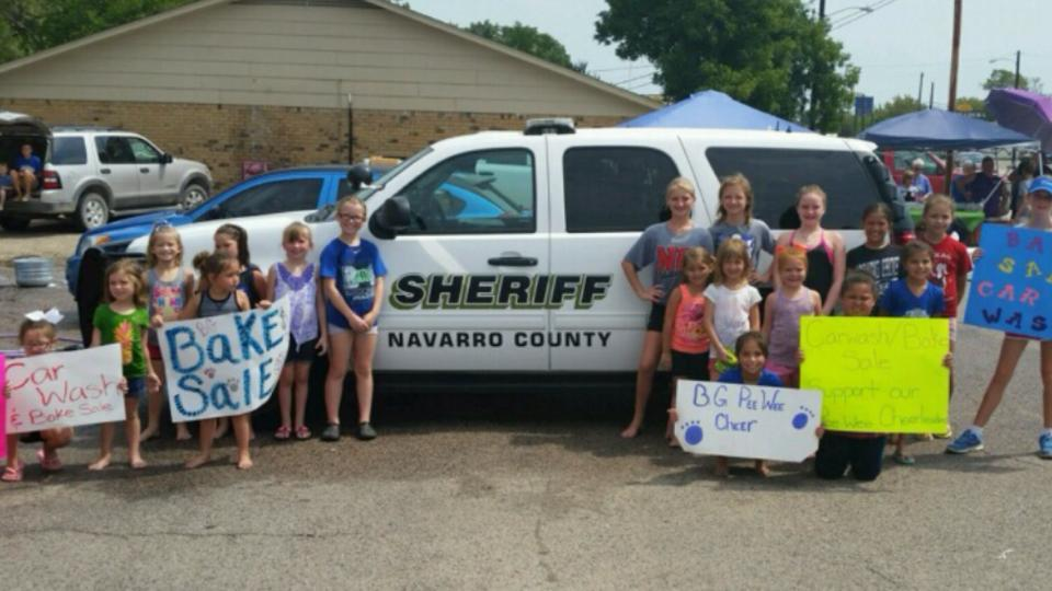 Blooming Grove peewee cheerleaders pose with NCSO police vehicle after washing it
