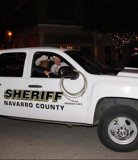 Navarro County Sheriffs Officers in vehicle participating in Corsicana Christmas Parade